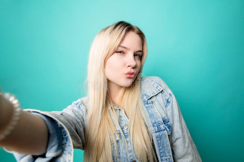 Positieve blond-haired vrouw die selfie op blauwe achtergrond nemen die pret met zich maken stock fotografie