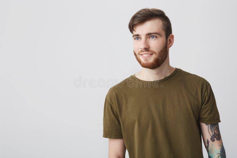 Positieve emoties Sluit omhoog portret van de knappe rijpe Europese gebaarde mens met blauwe binnen ogen en tatoegeringskoker stock foto's