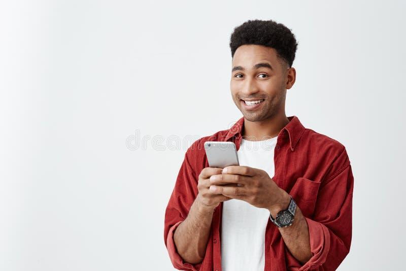 Positieve emoties Sluit omhoog van jong knap donker-gevild mannetje met afrokapsel in witte t-shirt en rood overhemd royalty-vrije stock foto