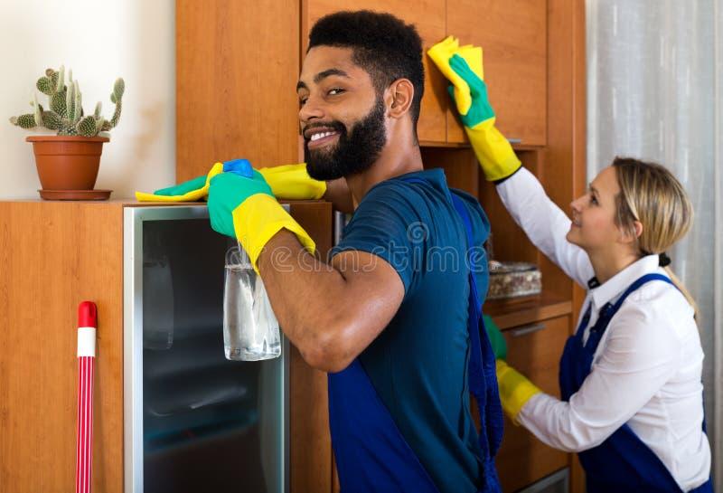 Positieve en reinigingsmachines die schoonmaken bestrooien stock fotografie
