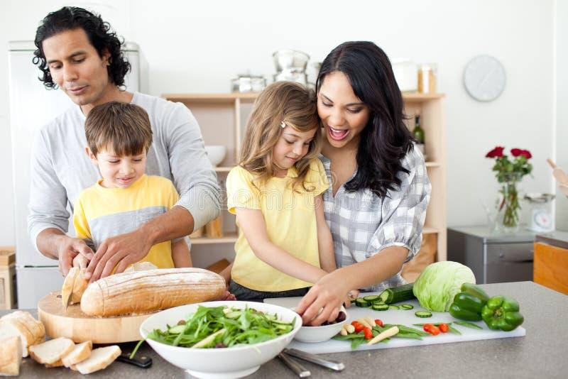 Positieve familie die lunch samen voorbereidt stock afbeeldingen