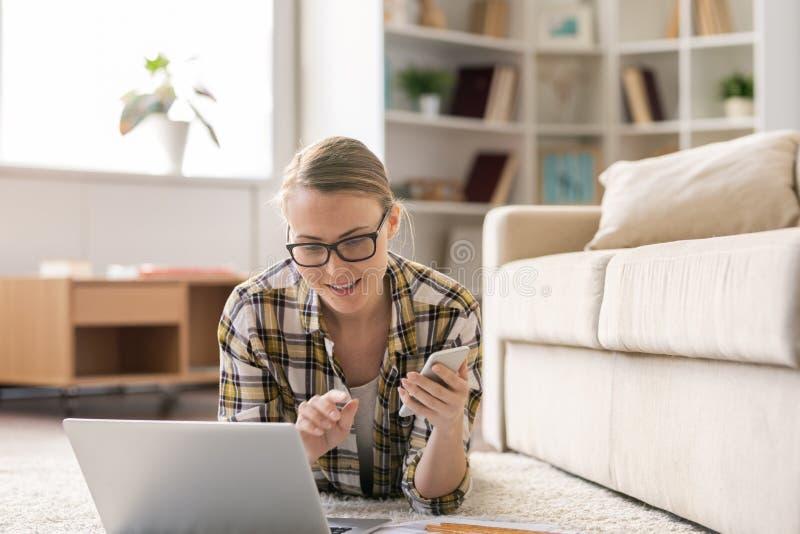 Positieve freelance vrouw die smartphone en laptop met behulp van stock afbeelding