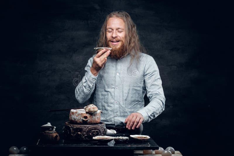 Positieve gebaarde mannelijke proevende thee stock fotografie
