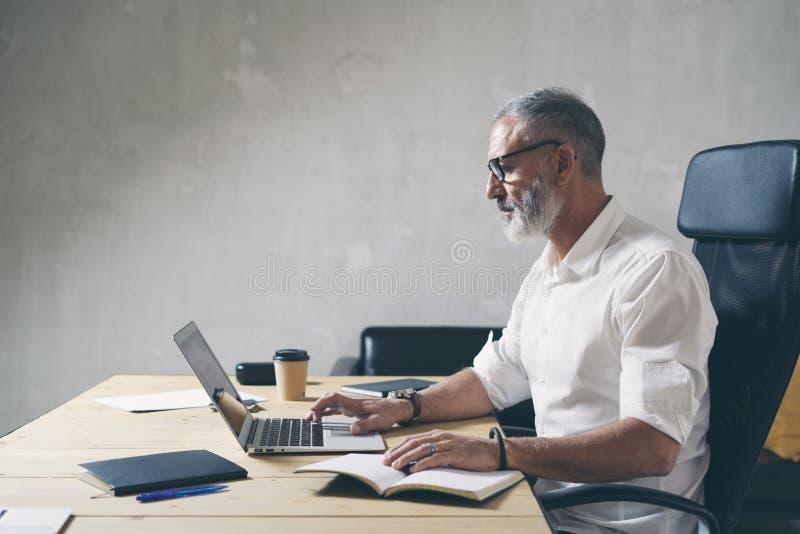Positieve gebaarde zakenman die mobiele laptop computer met behulp van terwijl het zitten bij houten lijst op moderne coworking p stock afbeelding