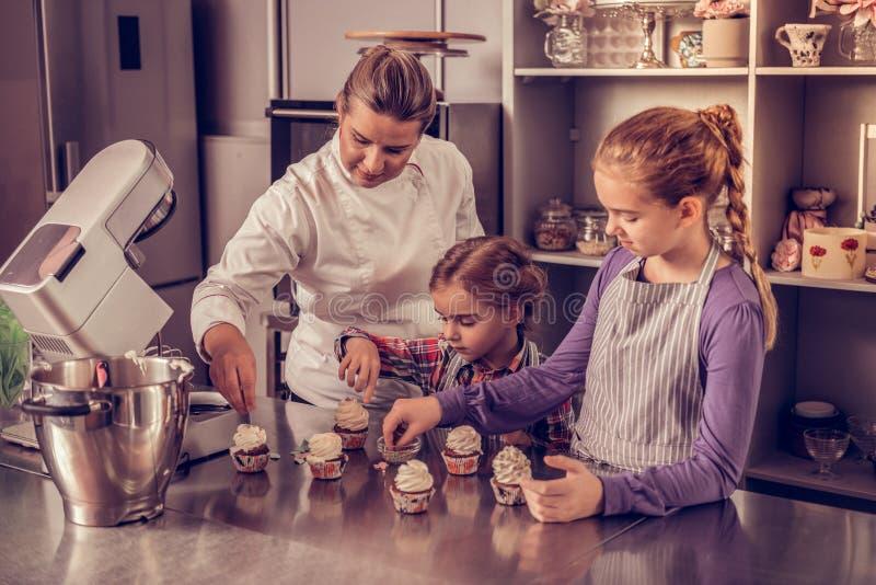 Positieve gebakjechef-kok die tonen hoe te verfraaien cupcakes royalty-vrije stock foto