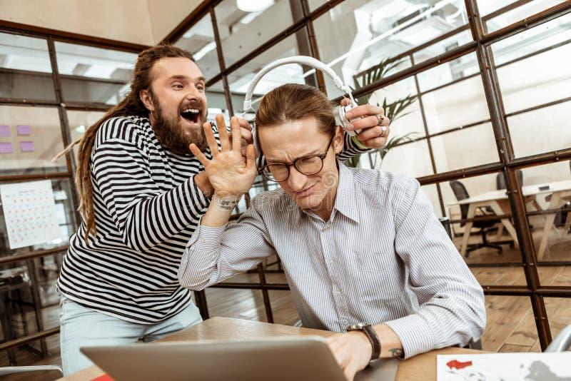 Positieve gelukkige gebaarde mens die witte hoofdtelefoons houden royalty-vrije stock afbeelding
