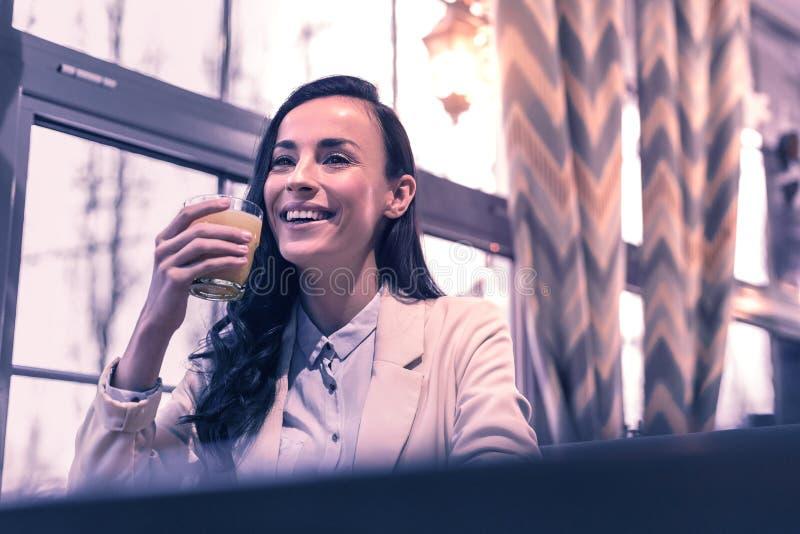 Positieve gelukkige vrouw die haar jus d'orange drinken stock foto