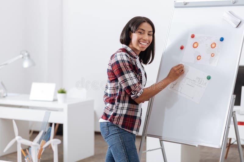 Positieve gelukkige vrouw die zich dichtbij whiteboard bevinden royalty-vrije stock fotografie