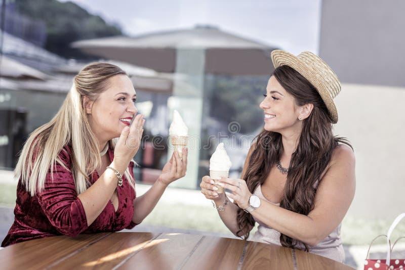 Positieve gelukkige vrouwen die hun roomijs eten stock foto's