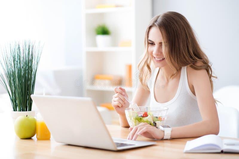 Positieve glimlachende vrouw die salade eten royalty-vrije stock foto