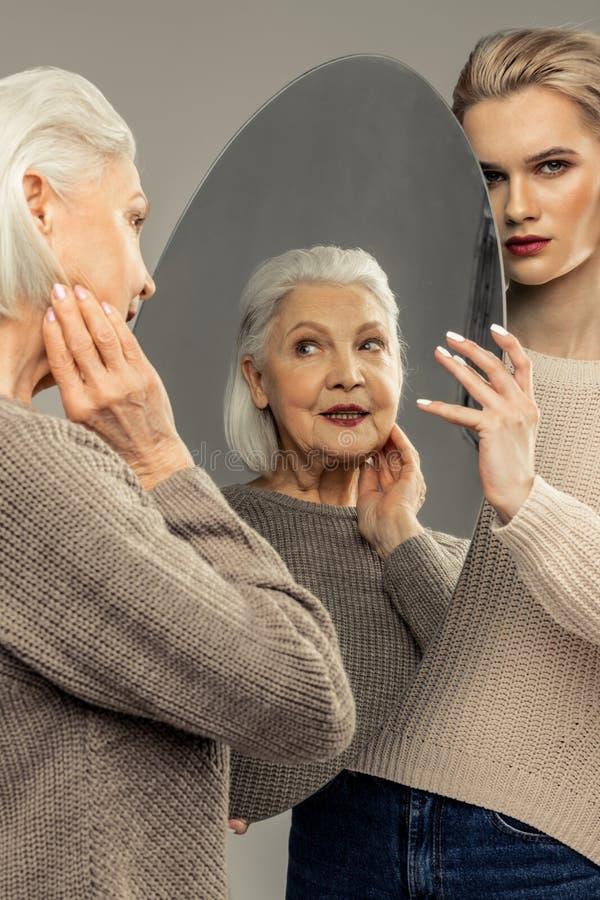 Positieve hogere vrouw die zich voor de spiegel bevindt royalty-vrije stock foto's
