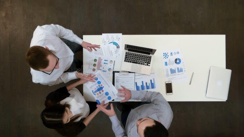 Positieve jonge bureauwerknemers die documenten bespreken op commerciële vergadering stock foto