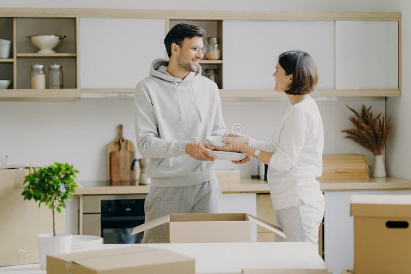 Positieve jonge man en vrouw pakken persoonlijke bezittingen uit in de keuken, dragen borden, kijken gladjes naar elkaar, steken  stock foto's