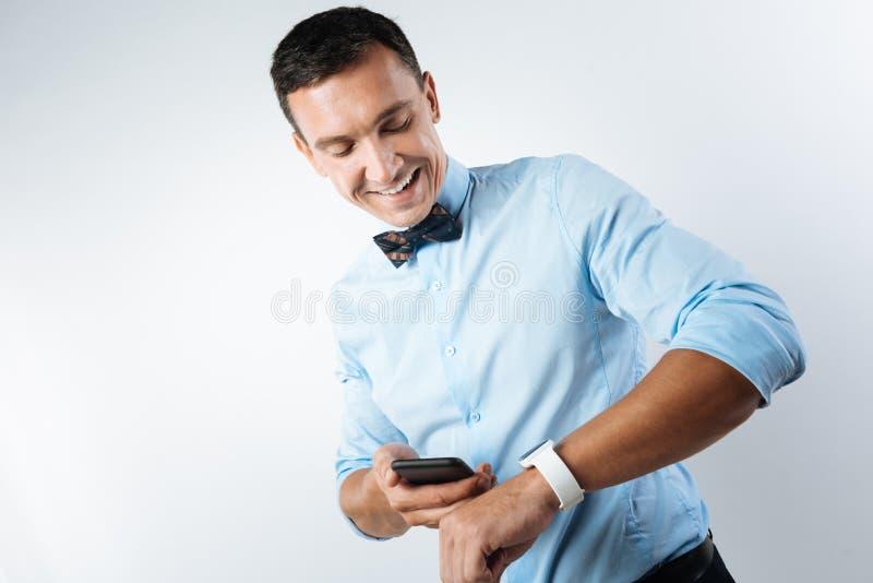 Positieve jonge mens die zijn smartwatch bekijken stock afbeelding