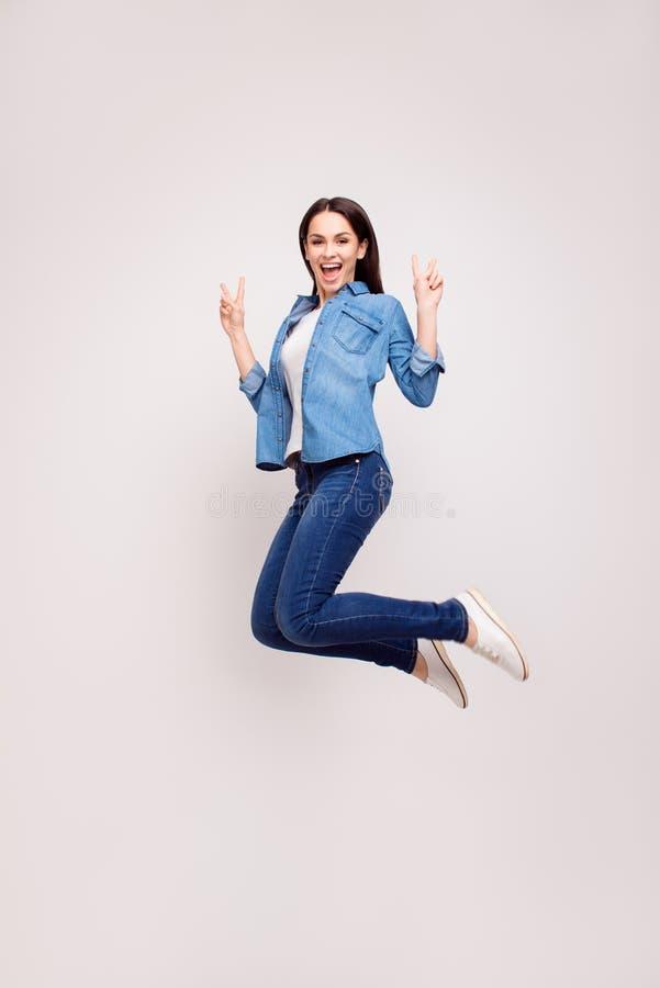 Positieve jonge mooie vrouw die in toevallige kleding omhoog springen en royalty-vrije stock afbeelding