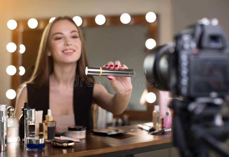 Positieve jonge vlogger toont nieuw schoonheidsmiddelenproduct stock foto's