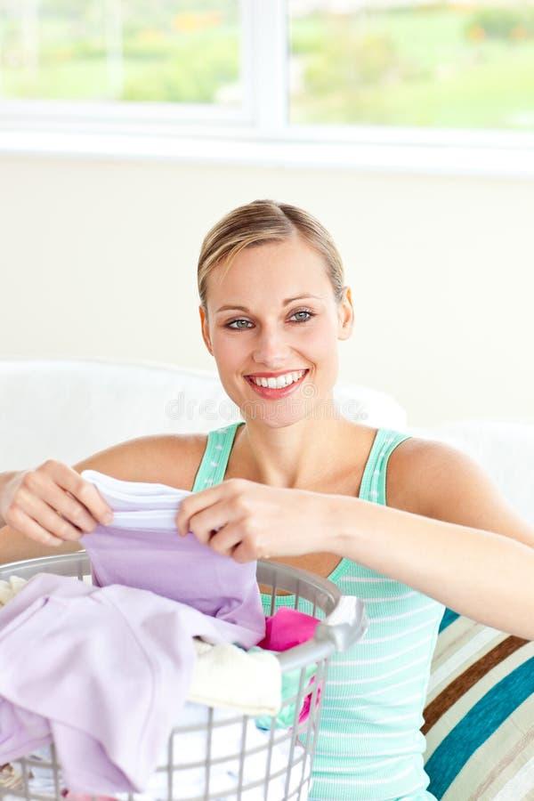 Positieve jonge vrouw die de wasserij doet stock foto