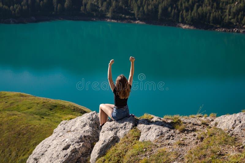 Positieve jonge vrouw die van vrijheid op de bovenkant van de berg met het meer geniet ritom als achtergrond stock afbeeldingen