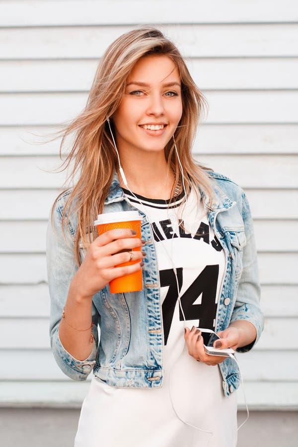 Positieve jonge vrouw met natuurlijke samenstelling met een mooie glimlach in een in blauw denimjasje in een witte T-shirt die ee stock foto