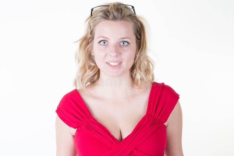 Positieve jonge vrouw in rode die kleding het glimlachen camera over witte achtergrond wordt geïsoleerd stock foto