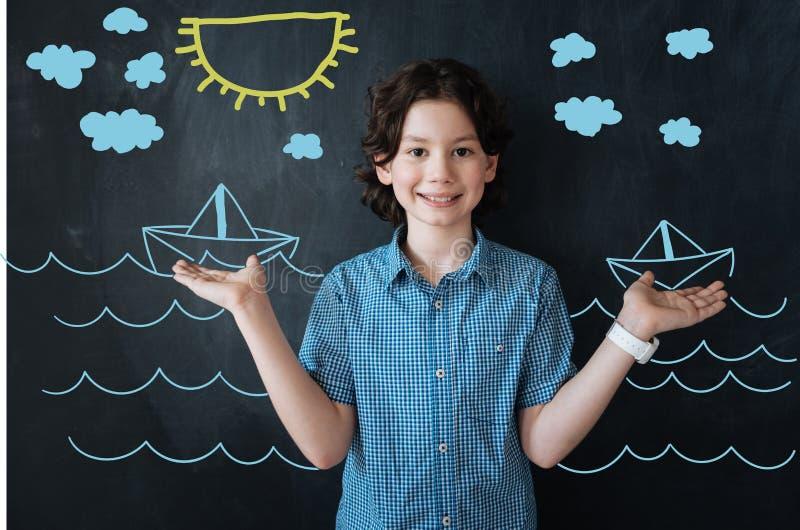 Positieve jongen die en terwijl het denken over schepen in het overzees glimlachen stock foto