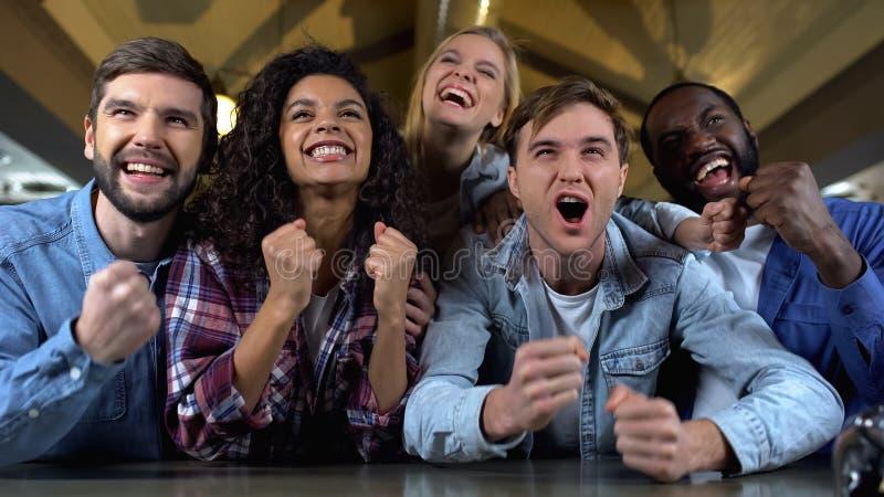 Positieve jongeren die voor teamdoel samen wortel schieten, het letten op gelijke, publiek stock foto