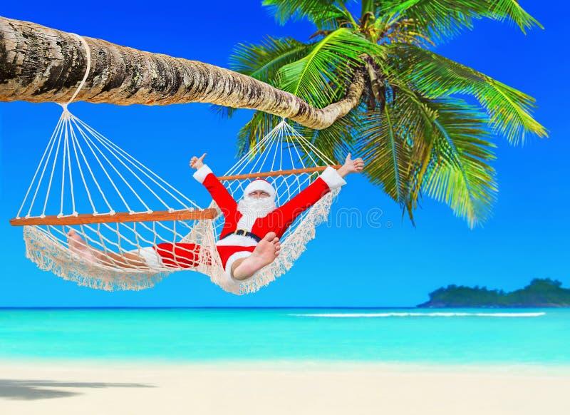 Positieve Kerstmis Santa Claus ontspant in hangmat in Palm Beach stock foto