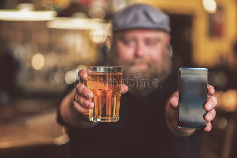 Positieve mannelijke het aantonen zaktelefoon en licht lagerbier met glimlach stock fotografie