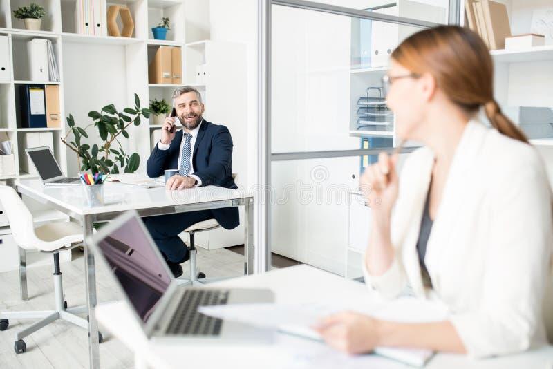 Positieve mannelijke manager die met collega overleggen terwijl langs het spreken royalty-vrije stock fotografie