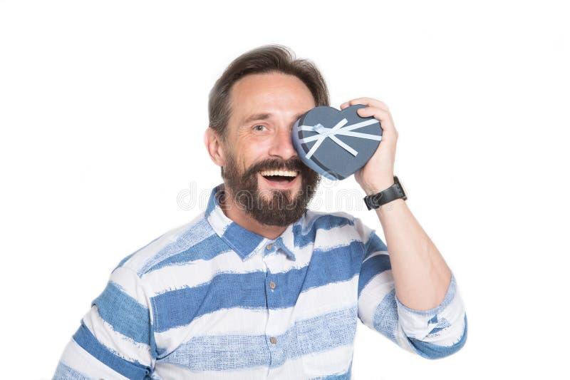 Positieve mens die hart gevormde doos zetten aan zijn gezicht en het glimlachen royalty-vrije stock afbeeldingen