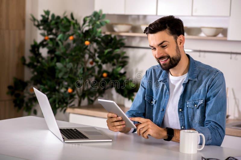 Positieve mens die zijn tablet gebruiken stock fotografie