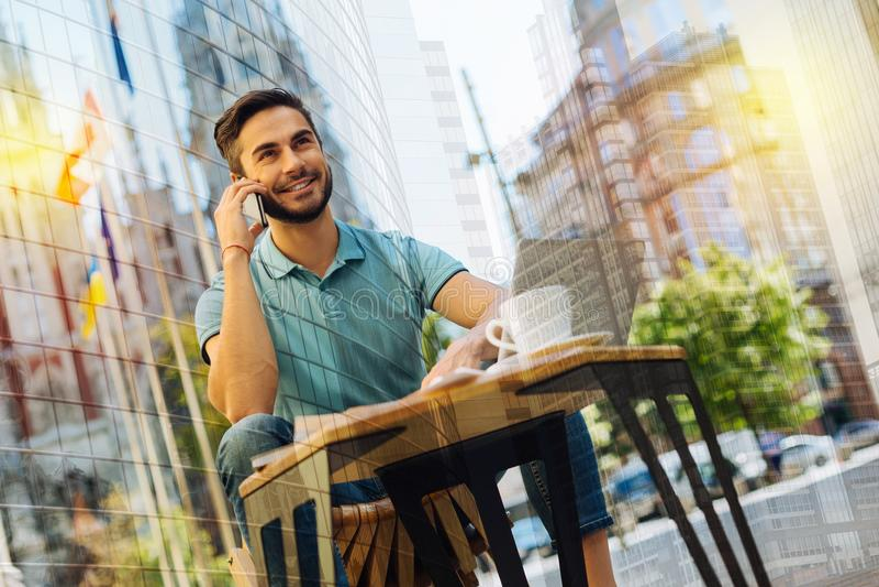 Positieve mens die zijn vriend telefoneren en hem uitnodigen om koffie samen te drinken royalty-vrije stock foto's
