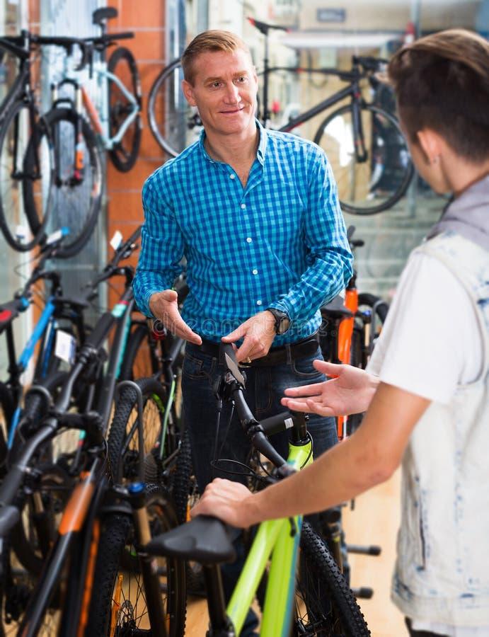 Positieve mens en jongenstiener die nieuwe fiets plukken stock afbeeldingen