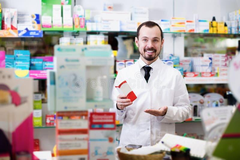 Positieve mensenapotheker die pillen tonen stock afbeelding