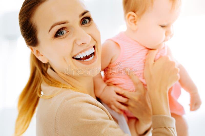 Positieve moeder die emotioneel terwijl het houden van haar baby zijn royalty-vrije stock foto's