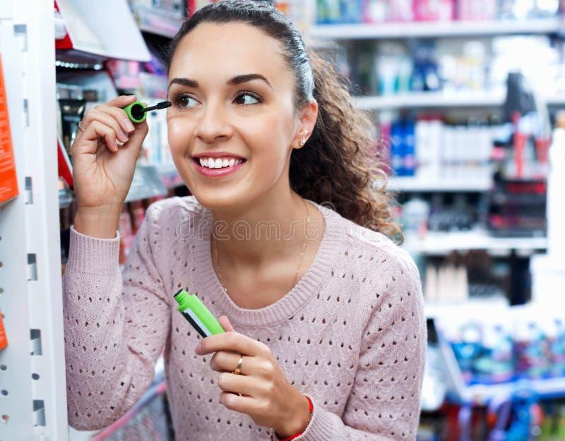 Positieve mooie vrouwelijke klant het kopen mascara royalty-vrije stock afbeelding
