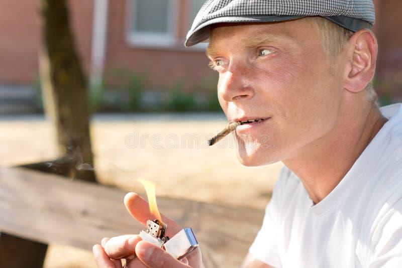 Positieve nadenkende mens die een bruine sigaret aansteken royalty-vrije stock foto's