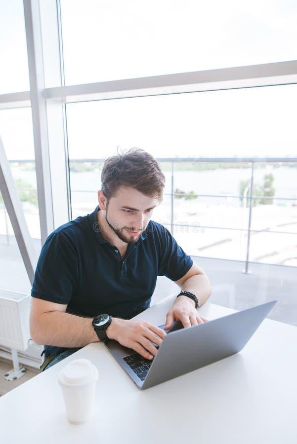Positieve onderneemsterzitting bij een lichte koffie bij het venster en het gebruiken van laptop stock foto