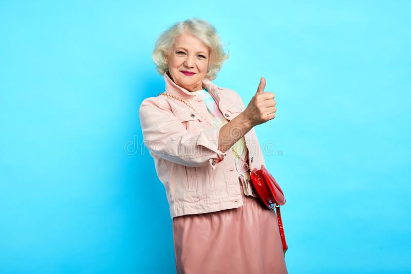 Positieve ontzagwekkende vrolijke oude dame die duim tonen royalty-vrije stock afbeelding