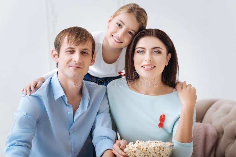 Positieve opgetogen familie die rode linten dragen stock afbeelding