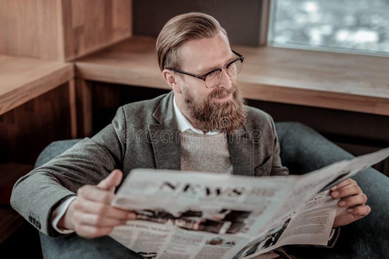 Positieve opgetogen gebaarde mens die interessant artikel lezen royalty-vrije stock fotografie