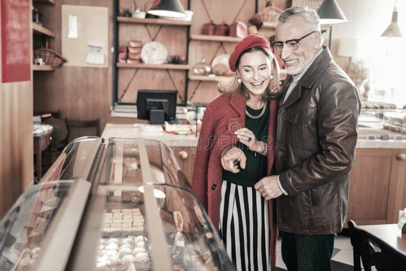 Positieve opgetogen rijpe mensen die snoepjes voor koffie kiezen stock afbeelding