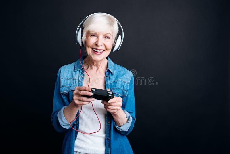 Positieve oude vrouw het spelen videospelletjes stock fotografie