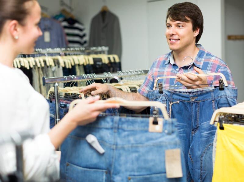 Positieve paar het kopen jeans in winkel stock afbeeldingen