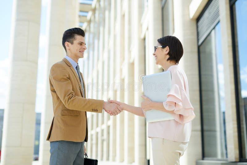 Positieve partners die elkaar begroeten royalty-vrije stock afbeelding
