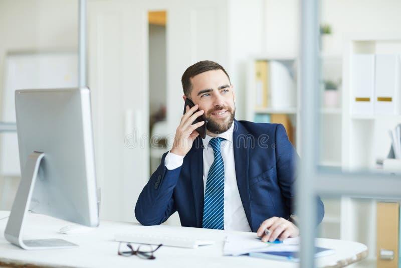 Positieve projectleider die plannen op telefoon bespreken stock foto