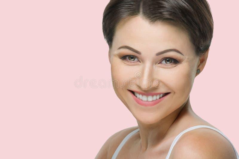 Positieve rijpe donkerbruine vrouw met mooie witte glimlach dichte omhooggaand op roze pastelkleurachtergrond royalty-vrije stock foto