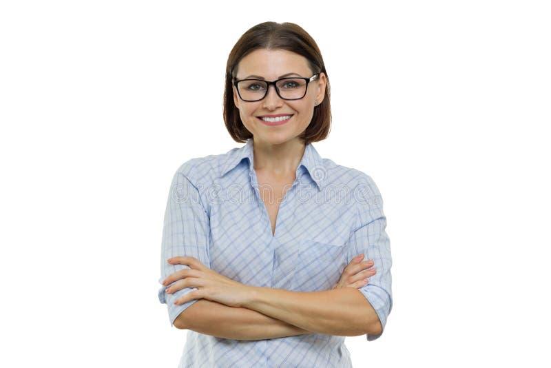 Positieve rijpe vrouw op wit geïsoleerde achtergrond Zekere vrouwelijke het glimlachen gekruiste wapens, onderneemsters, speciali stock fotografie