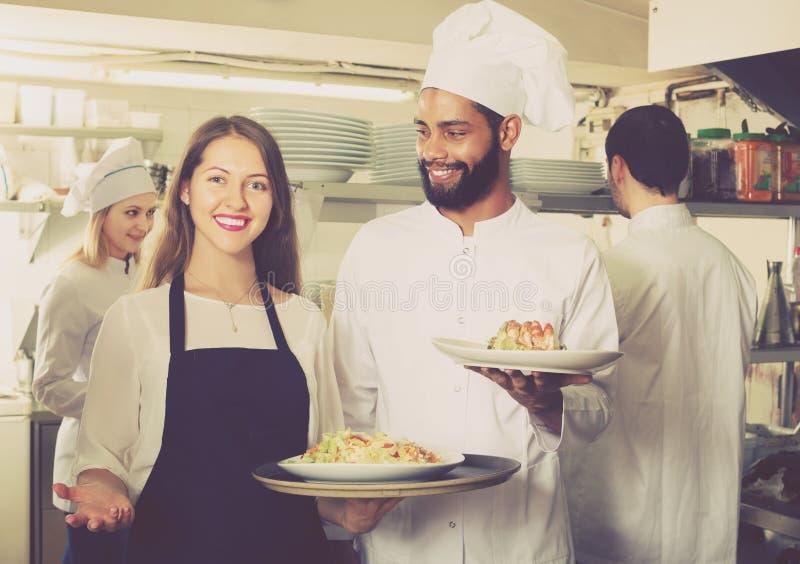 Positieve serveerster en kokend team royalty-vrije stock afbeeldingen