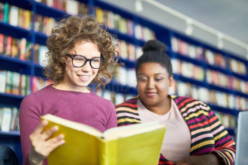 Positieve studenten die boek samen leren royalty-vrije stock afbeelding